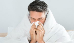 Man blowing his nose with covers around his shoulders who plans to schedule an online urgent care appointment with Doctor Online Oklahoma