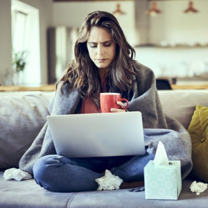 Woman sitting on a couch who is sick and using her computer to schedule an online doctor appointment with Doctor Online Oklahoma