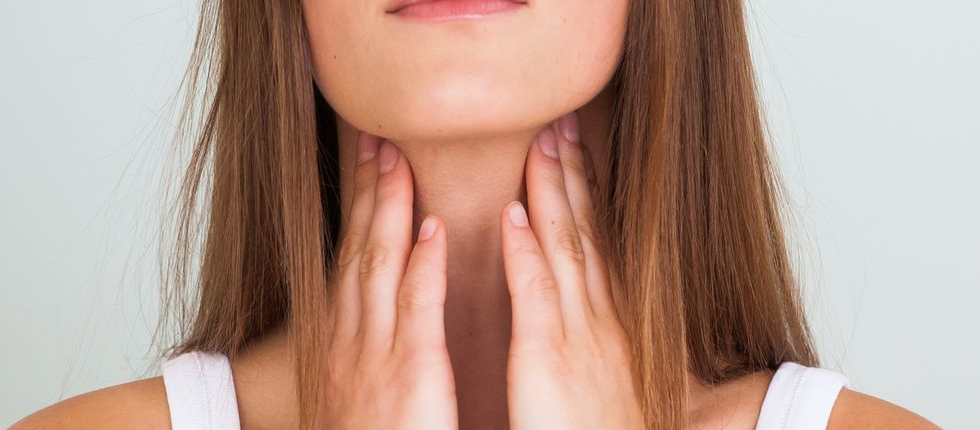 Woman with a sore throat, checking her swollen glands, and she plans to do an online doctor visit with Doctor Online Oklahoma